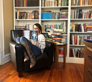 A.S. reading book in chair